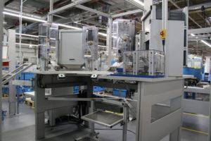 Elektrisch höhenverstellbarer Montagearbeitsplatz mit integrierter Mini-Hubtür und Kippbox